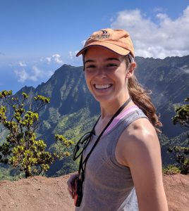 Elle smiling at the top of Pu'u'okila overlook into the Kalalau Valley